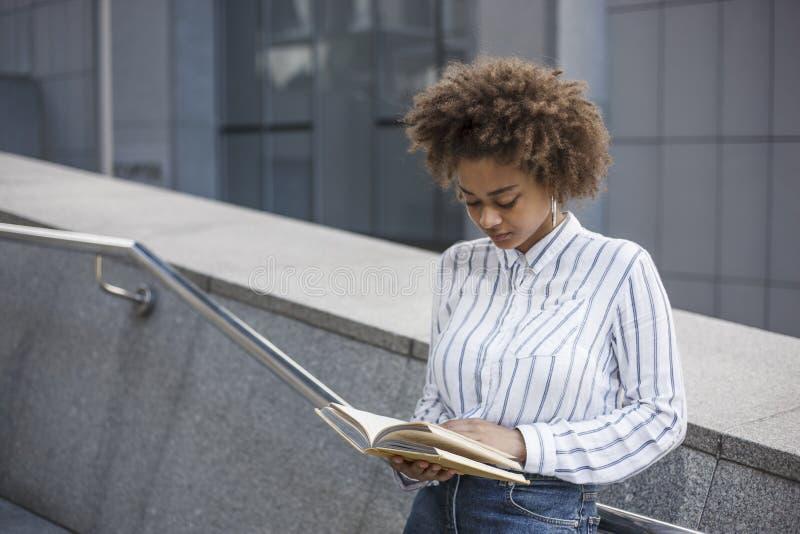 Den mörkhyade flickan står på momenten som lutar på räcket Hon läser en bok i gatan nära kontoret arkivfoton