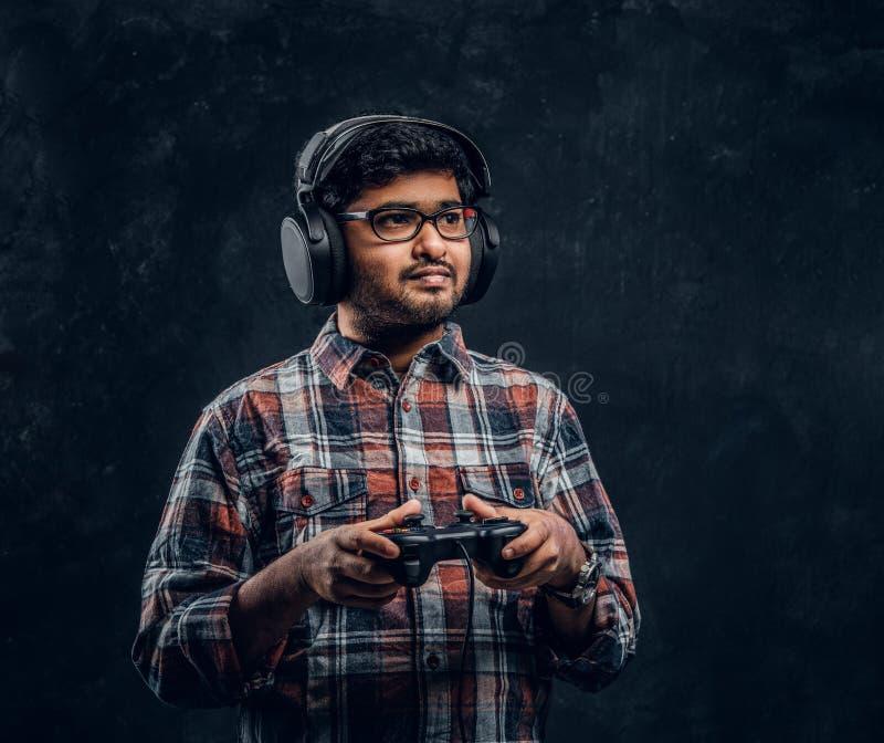 den mörkhyade gameren i hörlurar håller den modiga styrspaken arkivbilder