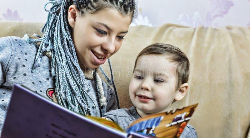 Den mörkhyade mamman läser en bok till hans lilla son Begrepp: Barnuppfostran familjevärderingar dagblomman ger mödrar mumsonen t royaltyfri fotografi