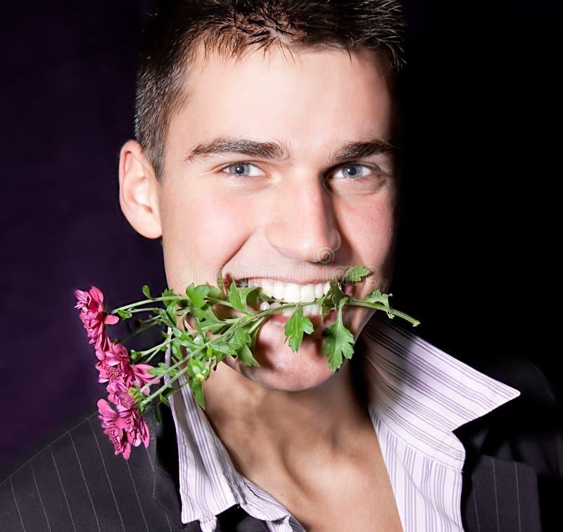 Den macho mannen rymmer i mun en blomma fotografering för bildbyråer