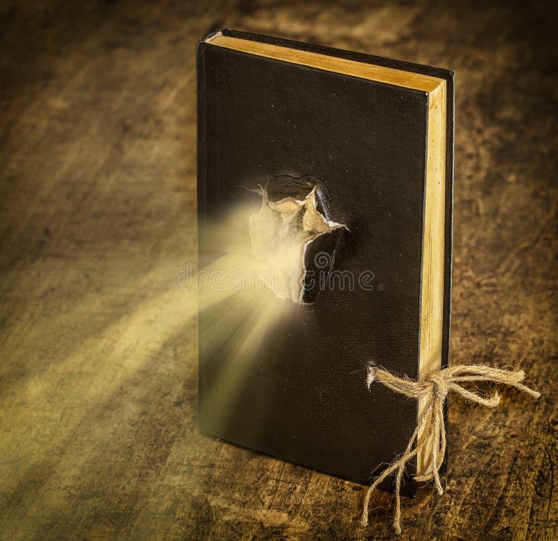 Den magiska boken som stängs på repet, sänder ut ljus arkivfoton