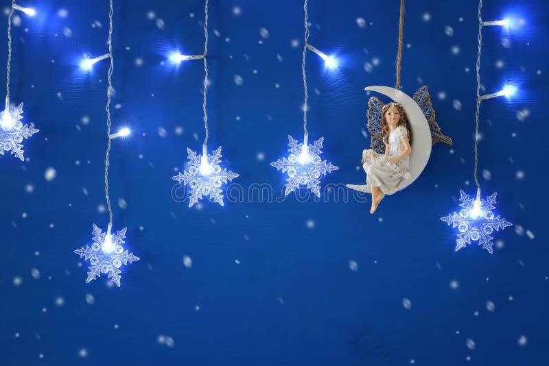 Den magiska julbilden av den lilla vita fen med blänker vingar som sitter på månen över blå bakgrund och, försilvrar snöflingagar arkivfoton