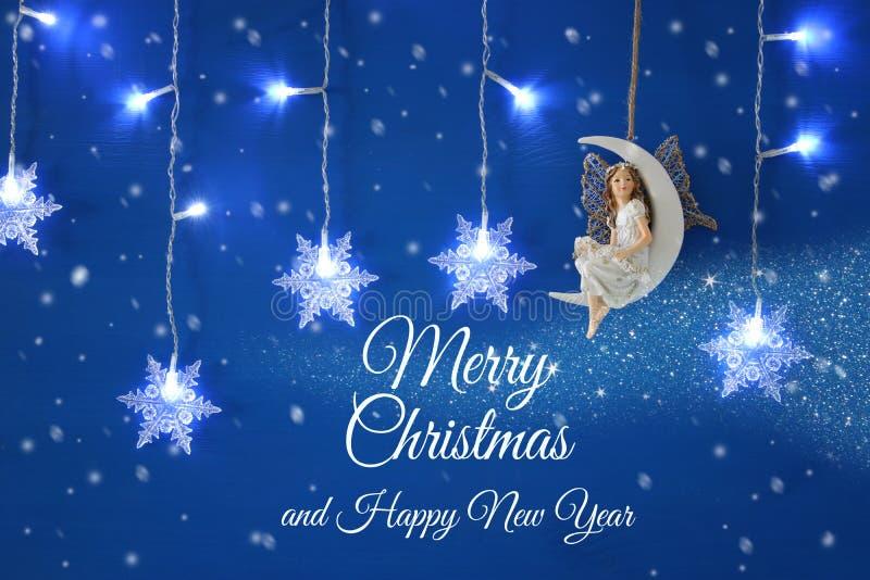 Den magiska julbilden av den lilla vita fen med blänker vingar som sitter på månen över blå bakgrund och, försilvrar snöflingagar royaltyfri foto