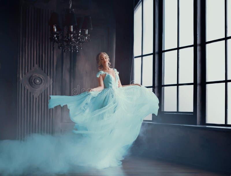 Den magiska omformningen av Cinderella in i en härlig prinsessa i en lyxig klänning Unga kvinnor är blonda royaltyfri foto
