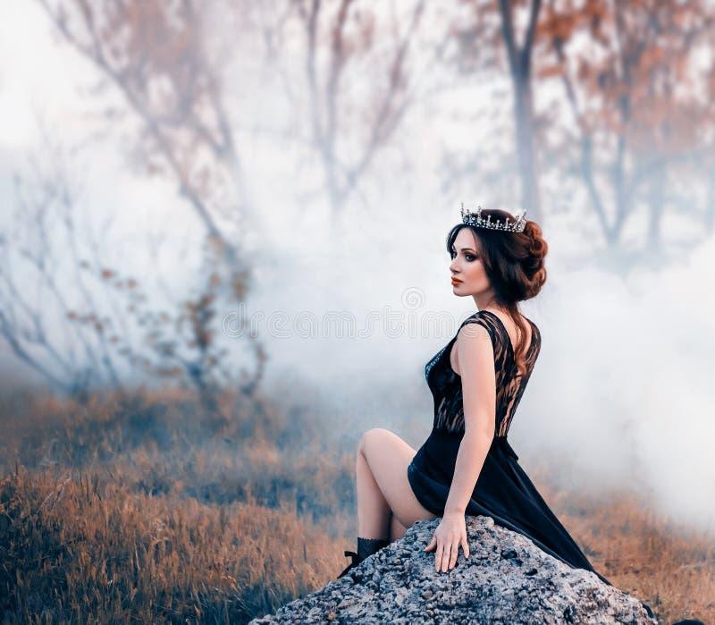 Den majestätiska damen, den mörka drottningen, sitter på stenen som gör bar hennes ben Brunettflickan i den gotiska kronan _ royaltyfria foton