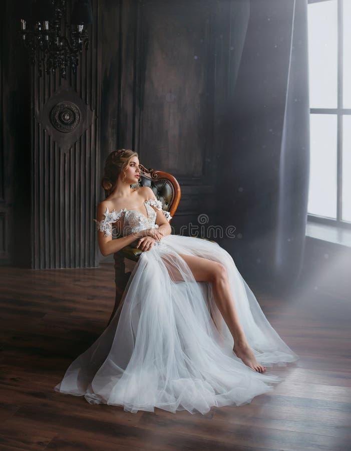 Den majestätiska och stolta prinsessaflickan i trött sammanträde för vit chic orientalisk vit silverklänning på stol, dam visar a royaltyfri foto