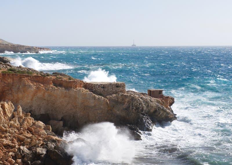Den maltesiska kustlinjen med vaggar och det stormiga havet, stor storm i den guld- solnedgången, varmt aftonljus, landskapet, ma arkivfoto
