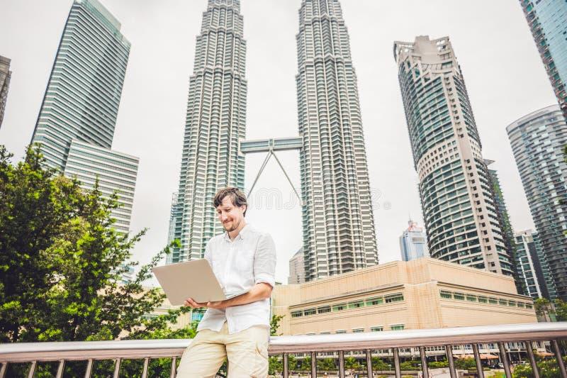 Den manaffärsmannen eller studenten i den tillfälliga klänningen som använder bärbara datorn i ett tropiskt, parkerar på bakgrund royaltyfri fotografi