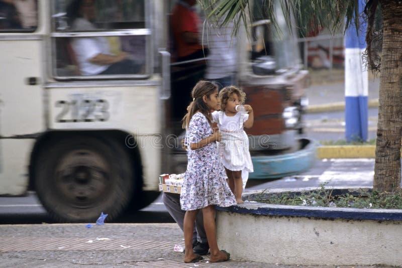Den Managua gatasikten, gatabarn och staden bussar royaltyfria bilder