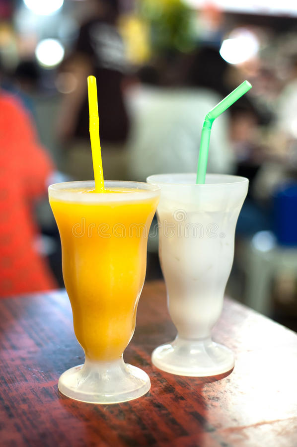 Den mangosmoothien och kokosnöten mjölkar drinkar som tjänas som på en thailändsk restaura fotografering för bildbyråer