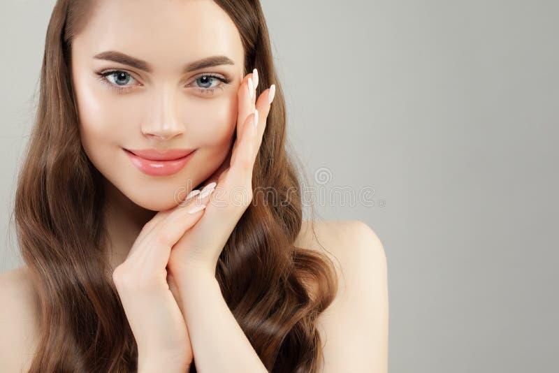 Den manicured Spa modellkvinnan med klar hud och spikar på grå banerbakgrund royaltyfri foto