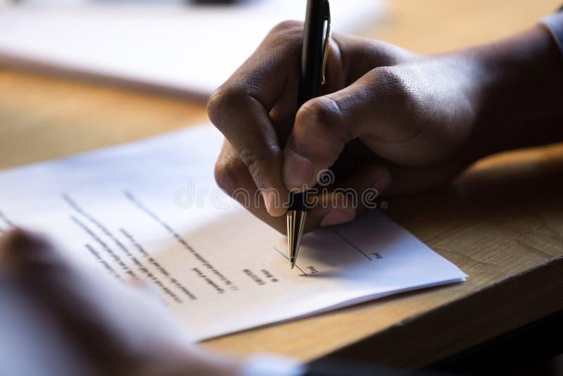 Den manliga afrikanska handen skriver häftet på lagligt företags papper docum fotografering för bildbyråer