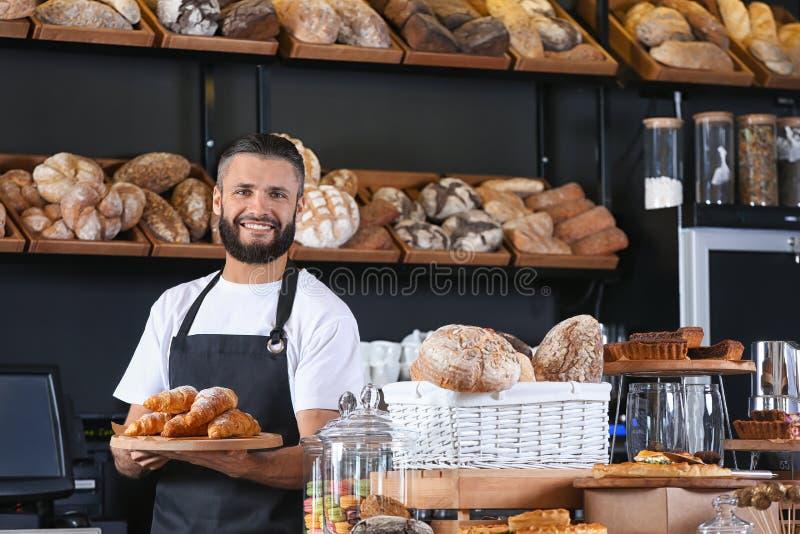 Den manliga bagaren som rymmer träbrädet med läckra giffel shoppar in arkivfoton