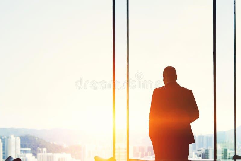Den manliga bankiren står nära fönstret av en skyskrapa med kopieringsutrymme arkivfoto
