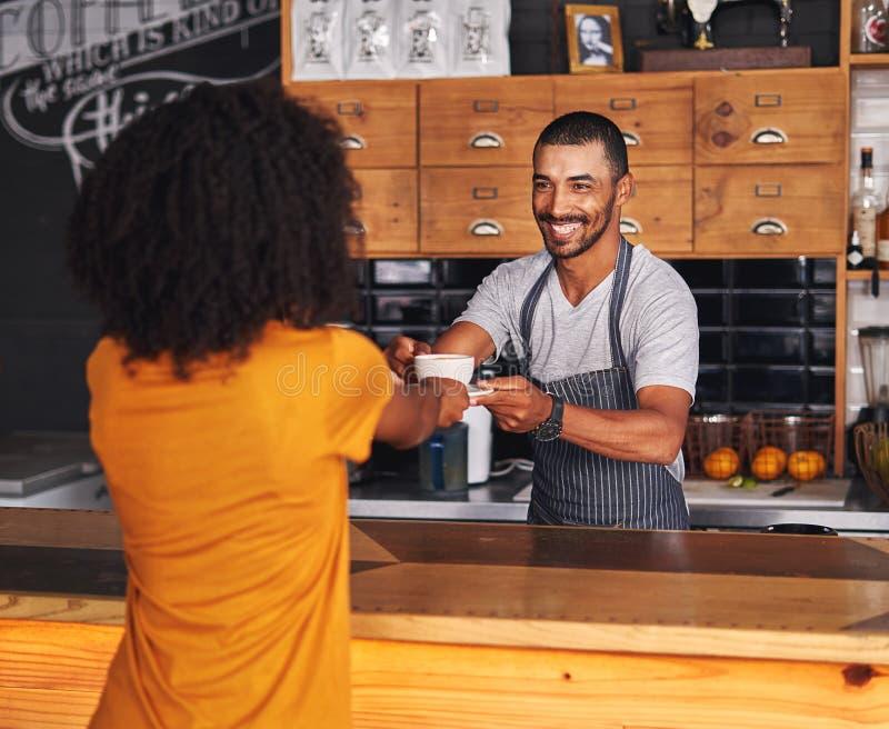 Den manliga baristaen erbjuder varmt kaffe till den kvinnliga kunden arkivbild