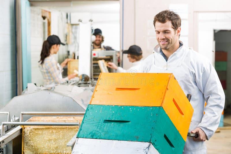 Den manliga beekeeperen Holding Trolley Of staplade royaltyfria bilder