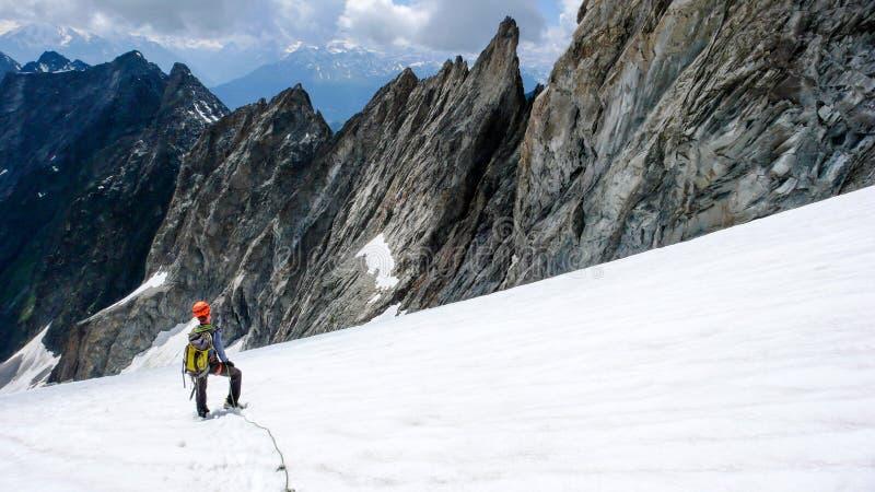Den manliga bergsbestigaren tar ett avbrott på en hög alpin glaciär och ser hans nedgång och nedstigningsrutten royaltyfri foto