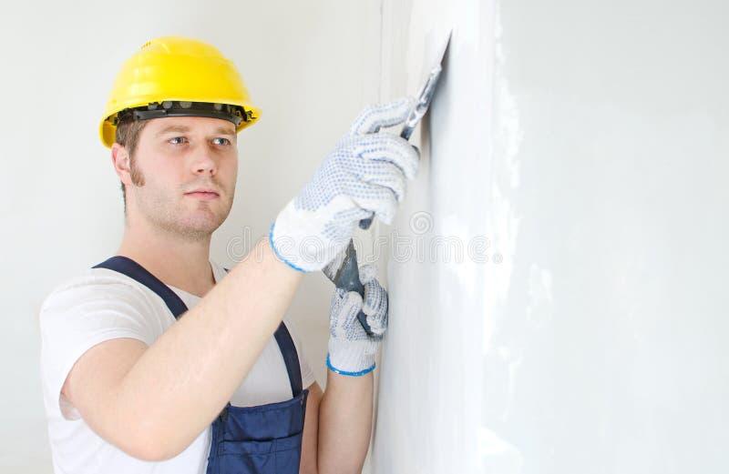 Den manliga byggmästaren reparerar väggen arkivbild