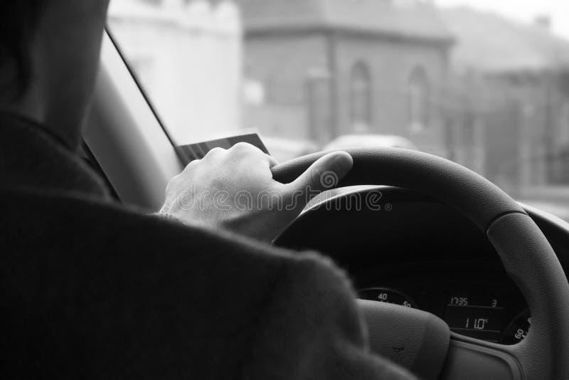 Den manliga chauffören räcker det hållande styrninghjulet Körning av säkerhet i staden svart white för bakgrund royaltyfri fotografi