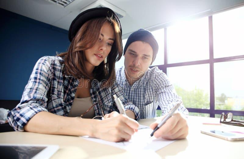 Den manliga chefen som sätter hans idéer och skriver affärsplan på arbetsplatsen, man hållande pennor och legitimationshandlingar royaltyfri fotografi