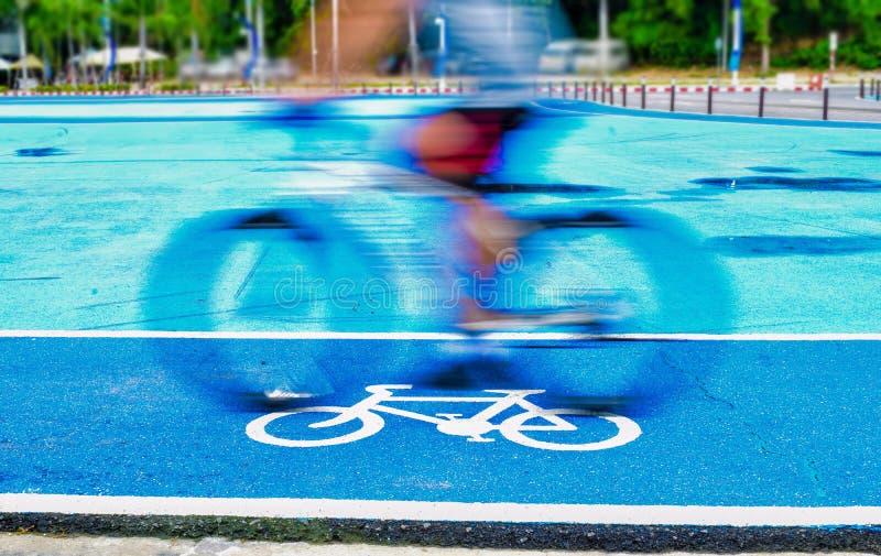 Den manliga cyklisten rider en cykel p? gr?nden av cykeltecknet arkivbilder
