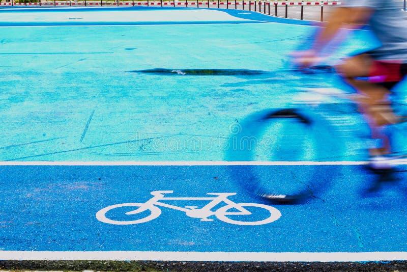 Den manliga cyklisten rider en cykel p? gr?nden av cykeltecknet royaltyfri fotografi
