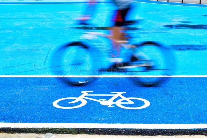 Den manliga cyklisten rider en cykel p? gr?nden av cykeltecknet royaltyfria foton