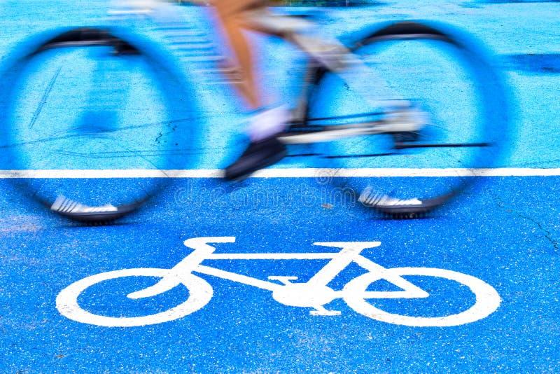 Den manliga cyklisten rider en cykel p? gr?nden av cykeltecknet arkivfoton