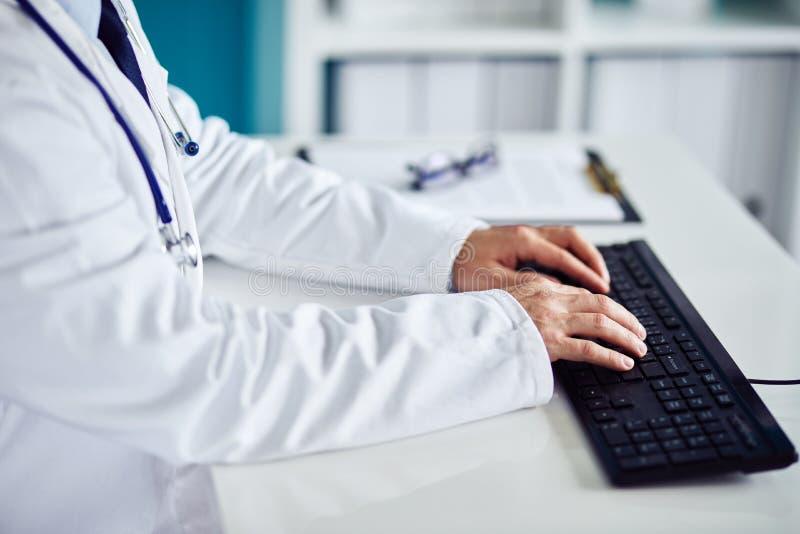 Den manliga doktorn arbetar med datoren arkivbilder