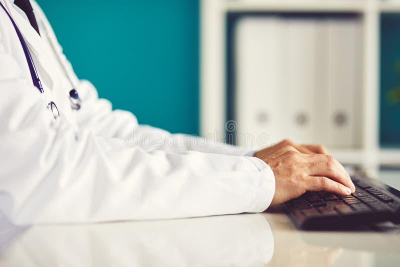 Den manliga doktorn arbetar med datoren arkivbild