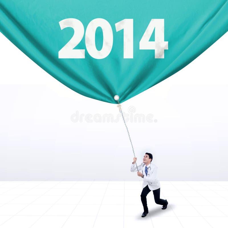 Den manliga doktorn drar ett baner av det nya året 2014 royaltyfri foto