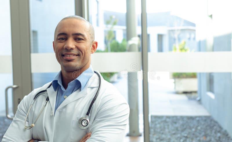 Den manliga doktorn med armen korsade att se kameran i sjukhus royaltyfri fotografi