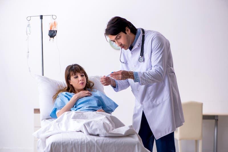 Den manliga doktorn som bes?ker den kvinnliga patienten avv?rjer in arkivfoto