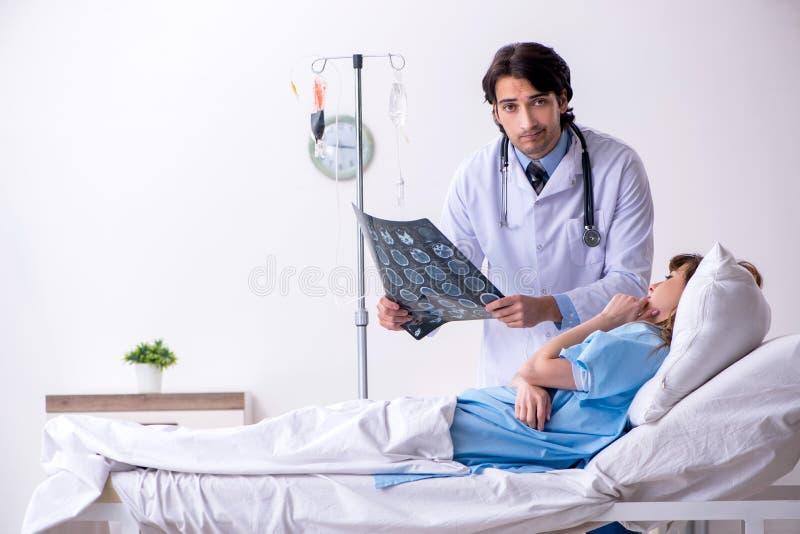 Den manliga doktorn som bes?ker den kvinnliga patienten avv?rjer in royaltyfria foton