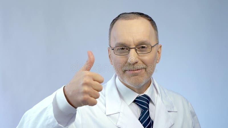 Den manliga doktorn som ler på kameran som gör tummar-upp, räcker tecknet, det bästa medicinska hjälpmedlet arkivbild