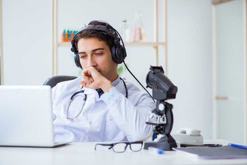 Den manliga doktorn som lyssnar till patienten under telemedicineperiod fotografering för bildbyråer