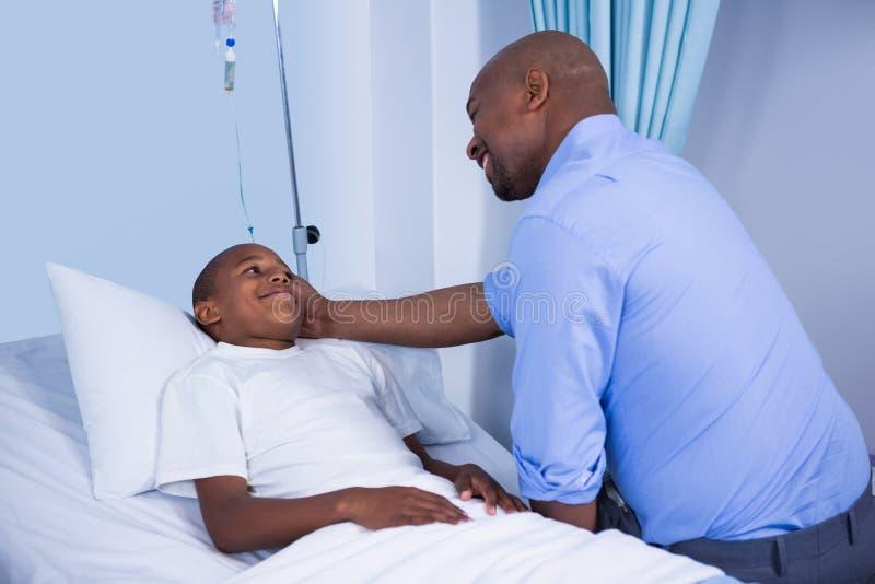 Den manliga doktorn som tröstar patienten under besök avvärjer in royaltyfri fotografi