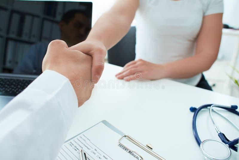 Den manliga doktorn tar omsorg till den kvinnliga patienten och lyckönskan för hans goda hälsor Doktor och patient som skakar hän royaltyfri foto