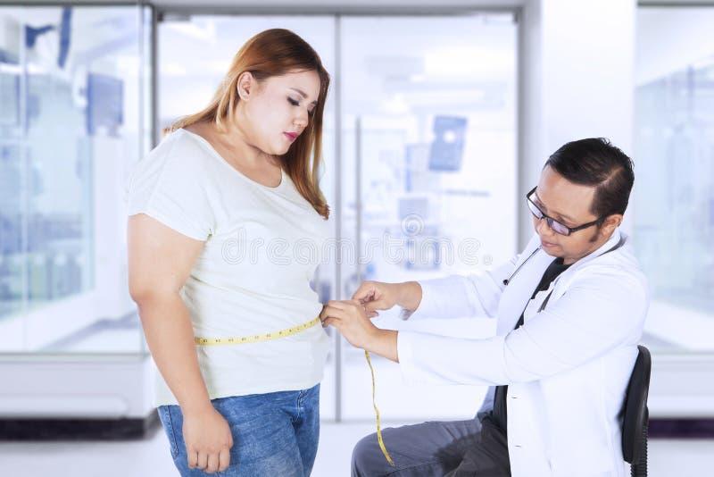 Den manliga doktorn undersöker en sjukligt fet kvinna i sjukhus royaltyfri fotografi