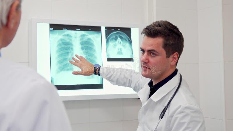 Den manliga doktorn visar något på röntgenstråle till hans kollega fotografering för bildbyråer