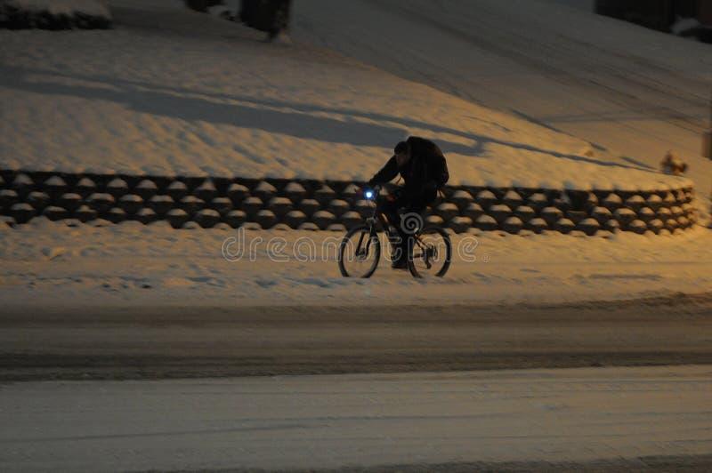 Den manliga den 15:e cyklar i nedgång för tung snö i afton i Lewiston royaltyfri bild