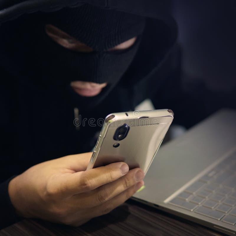 Den manliga en hacker i en svart maskering använder smartphonen och bärbara datorn En fraudster begår cyberbrott Bedräglig intrig royaltyfri fotografi