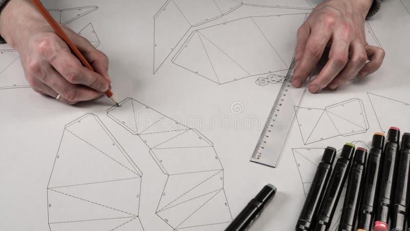 Den manliga formgivaren gör en funktionsduglig teckning Arbetsplats av en leksakformgivare Markörer, linjalen, pennan och blyerts royaltyfri foto