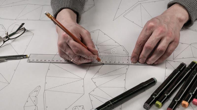 Den manliga formgivaren gör en funktionsduglig teckning Arbetsplats av en leksakformgivare Markörer, linjalen, pennan och blyerts royaltyfri bild