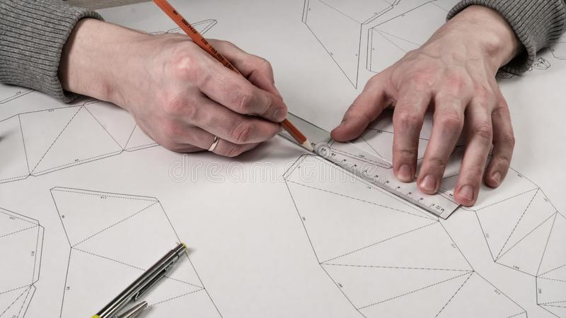 Den manliga formgivaren gör en funktionsduglig teckning Arbetsplats av en leksakformgivare Markörer, linjalen, pennan och blyerts arkivfoto