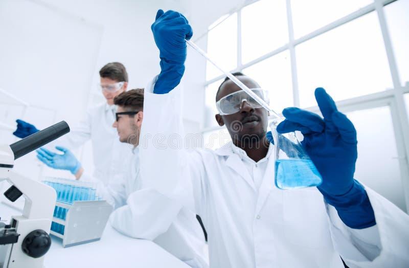 Den manliga forskaren med en flaska gör ett prov i laboratoriumet royaltyfria foton