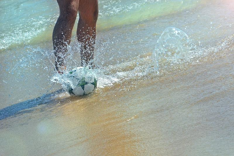 Den manliga foten sparkar en fotbollboll på vattnet Fotboll på stranden av medelhavet i Israel arkivbild