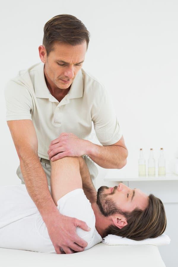 Den manliga fysioterapeuten som sträcker a, mans handen royaltyfria foton