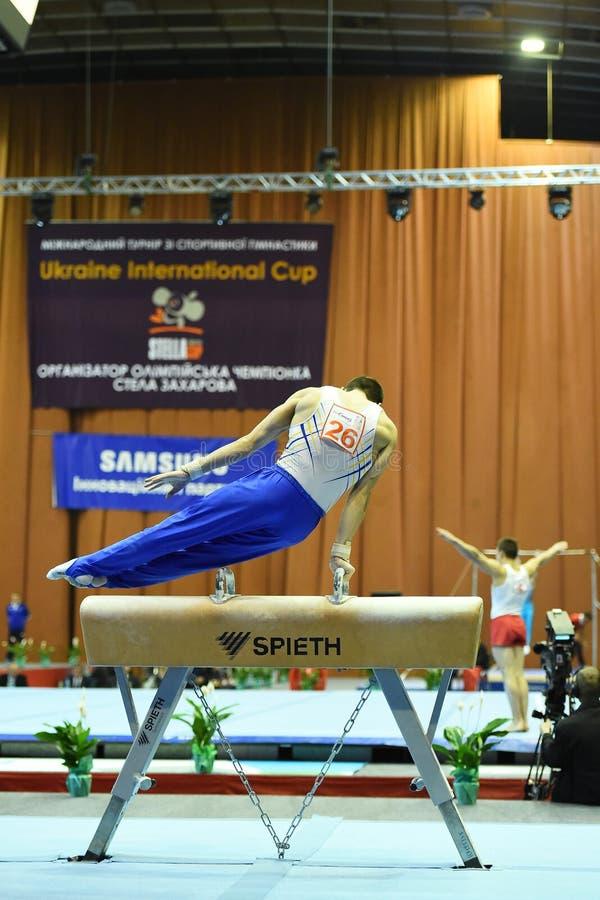 Den manliga gymnasten som utför på, pucklar på hästen royaltyfria bilder