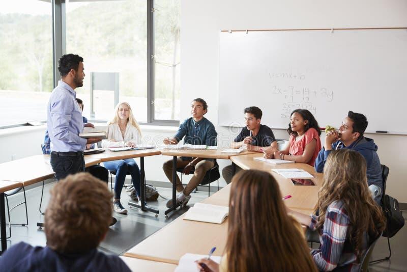 Den manliga högstadiet handleder With Pupils Sitting på grupp för tabellundervisningmatematik arkivfoto